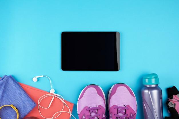 Tablet eletrônico com uma tela preta em branco, ao lado dele é roupas de fitness