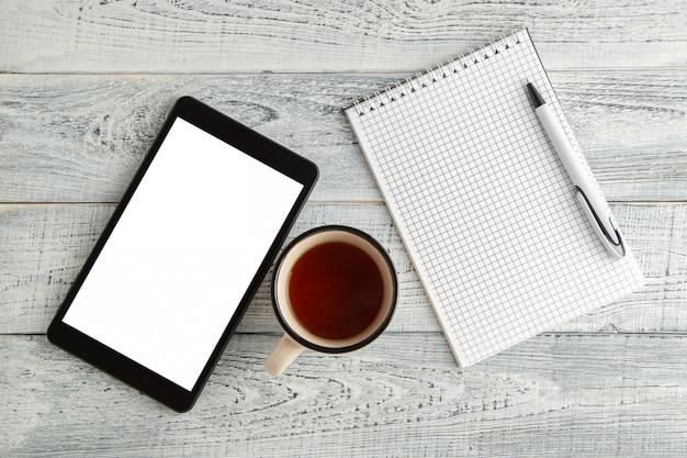 Tablet eletrônico preto, caderno de papel e uma xícara de chá ou café em uma madeira branca gasto vintage, vista superior
