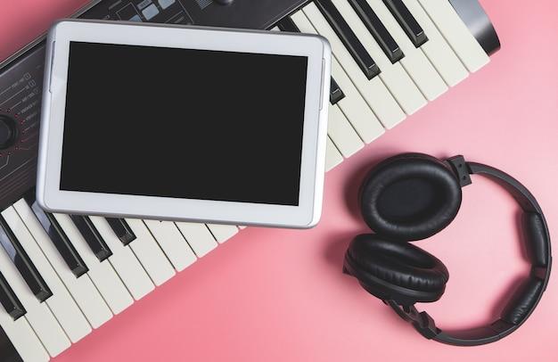Tablet em branco no teclado do estúdio para aplicação de música simulada