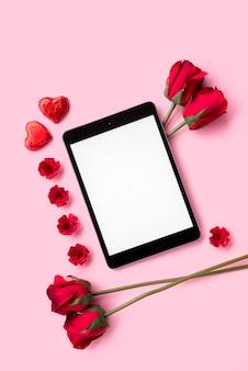 Tablet entre flores e corações de ornamento