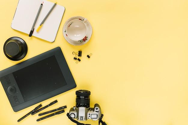 Tablet gráfico digital; câmera; papelaria e copo vazio em fundo amarelo