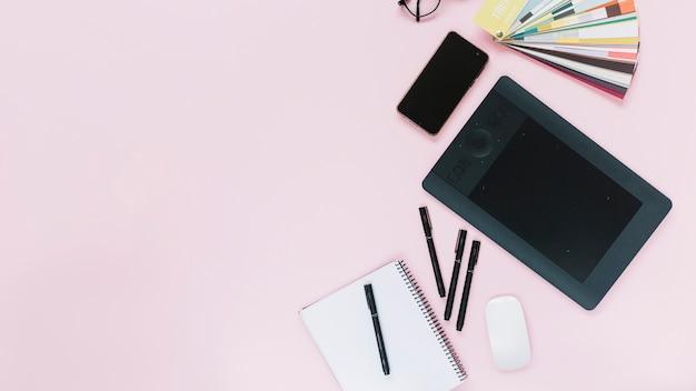 Tablet gráfico digital; celular e mouse com caderno espiral e canetas de feltro no fundo rosa