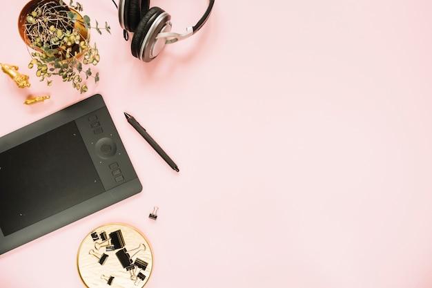 Tablet gráfico digital e caneta com showplant em fundo rosa