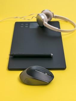 Tablet gráfico, fones de ouvido e mouse em uma mesa amarela. as ferramentas de um designer.