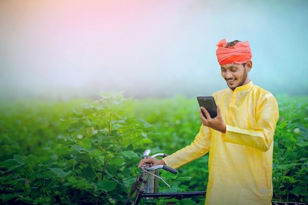 Tablet jovem agricultor indiano, índia rural.