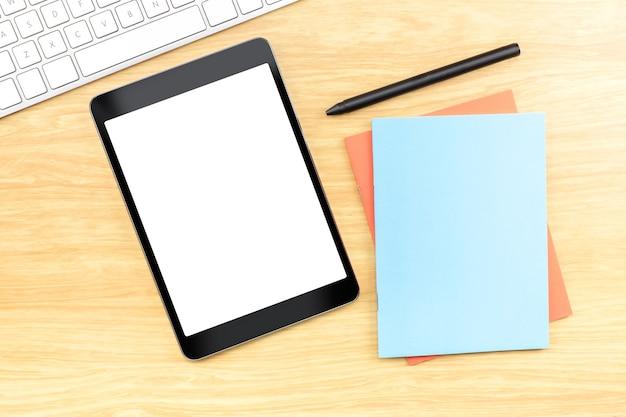 Tablet móvel de tela em branco com caderno azul e caneta na mesa de madeira