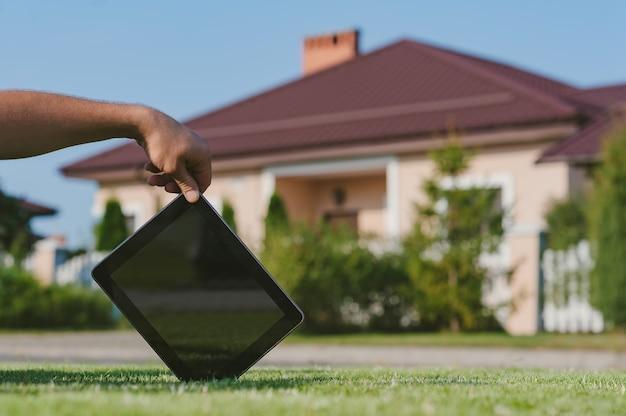 Tablet na mão, no gramado, contra o pano de fundo da casa.