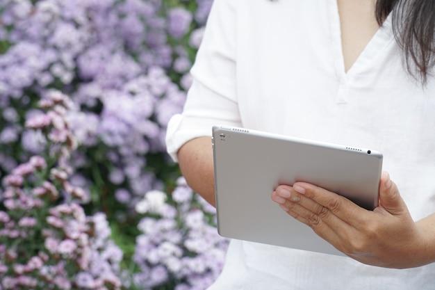Tablet nas mãos de uma mulher, cientista observando plantas de flores roxas.