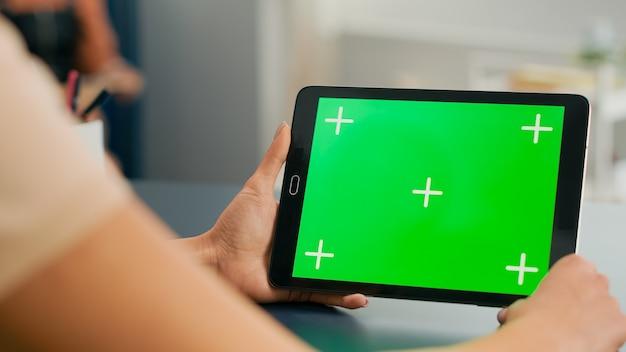 Tablet pc com simulação de exibição de chroma key de tela verde em pé na mesa da mesa. mulher freelancer navegando em um dispositivo isolado para comunicação on-line na web na sala de home office