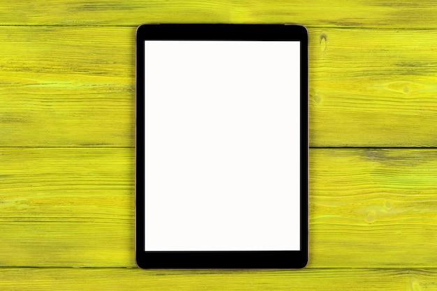 Tablet pc com simulação de tela em branco isolada no fundo da mesa de madeira amarela. tablet na mesa de madeira