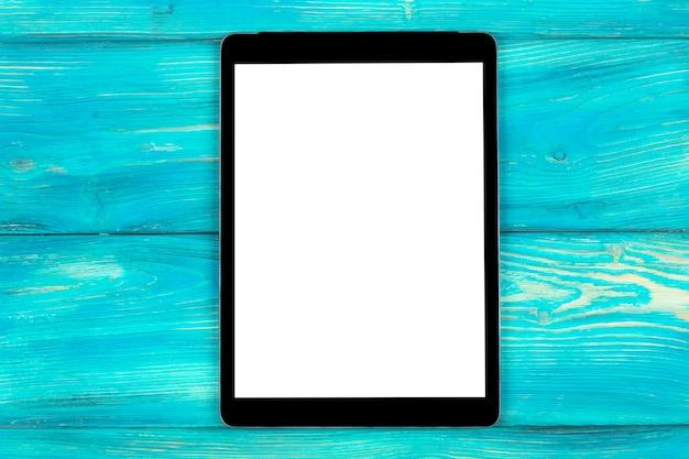 Tablet pc com simulação de tela em branco isolada no fundo da mesa de madeira azul. tablet na mesa de madeira. tela branca do tablet