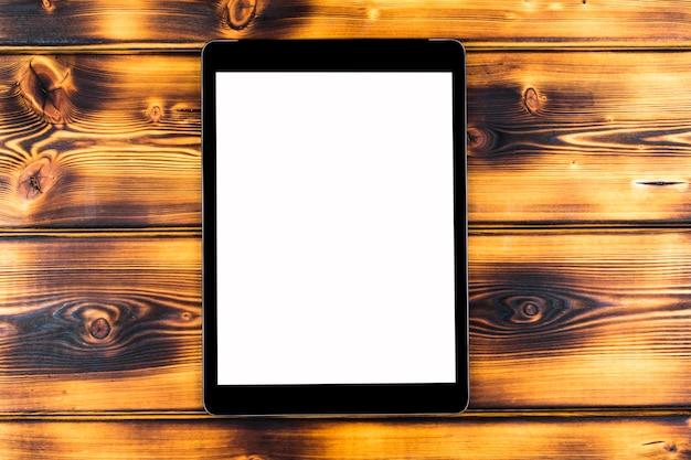 Tablet pc com simulação de tela em branco isolada no fundo da mesa de madeira queimada. tablet na mesa de madeira. tela branca do tablet