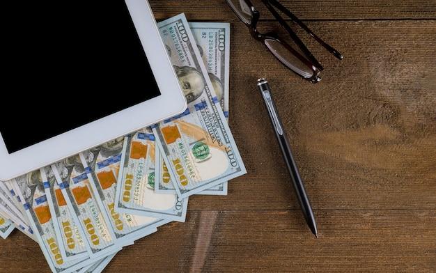 Tablet pc com uma caneta, óculos e notas de dólar em uma vista superior de mesa de madeira.