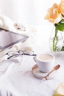 Tablet pc computador, xícara de café e bege rosas de manhã