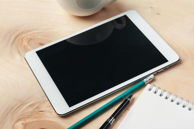 Tablet pc e xícara de café digitais na mesa de madeira.