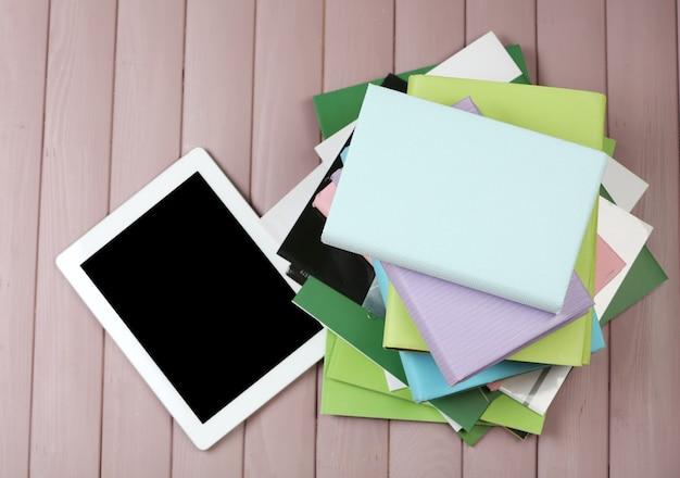 Tablet pc em cima de uma pilha de livros e revistas em um fundo de madeira