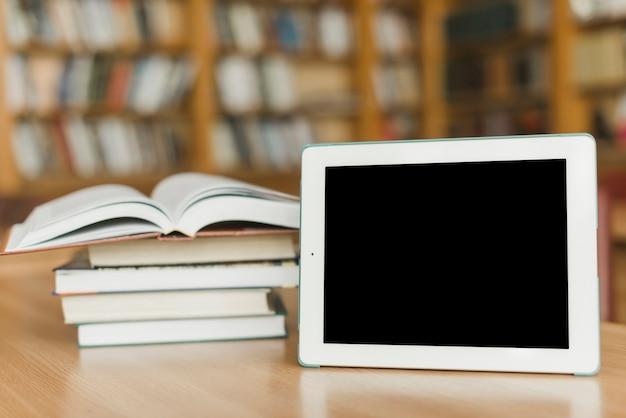 Tablet perto de pilha de livros