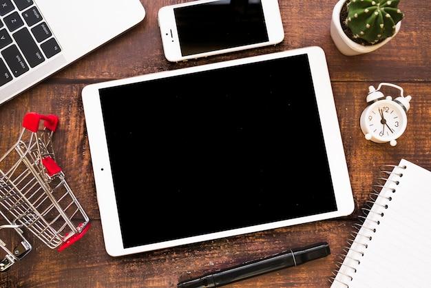 Tablet perto de smartphone, laptop e carrinho de compras