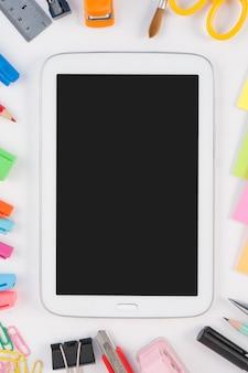 Tablet phone e escola ou ferramentas de escritório no fundo branco