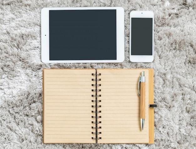 Tablet, smartphone e notebook no tapete macio