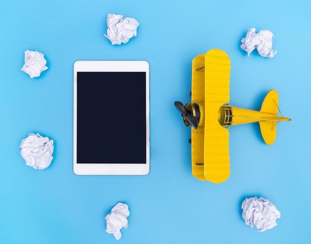 Tablet vazio em branco com o avião amarelo no céu de papel nuvem azul e branco para o conceito de viagens