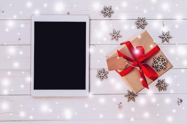 Tableta de visão superior e caixa de presente com neve, flocos de neve no fundo de madeira branca para o natal e o ano novo.