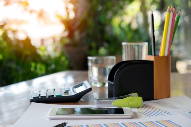 Tableta financeira com gráficos e equipamento de escritório na mesa
