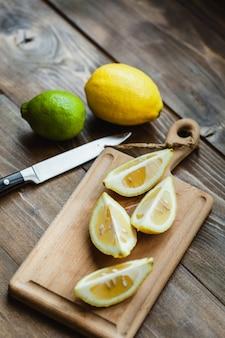 Tábua com limão e lima para fatiar, preparação para cozinhar, saladas e lanches, suco de limão, decoração de pratos, cozinhar
