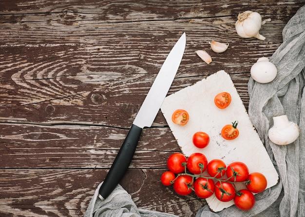 Tábua de cortar; cogumelo; tomates cereja e dentes de alho com faca no tampo da mesa de madeira