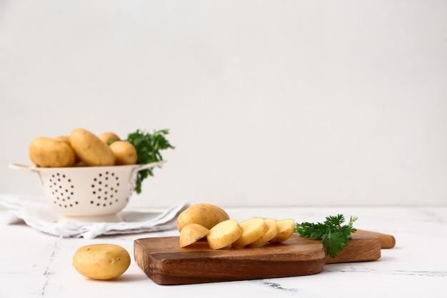 Tábua de cortar com batata crua e salsa na mesa