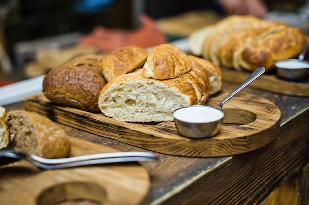Tábua de cortar com diferentes tipos de pão, molheira com manteiga