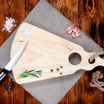 Tábua de cortar com uma faca em uma mesa de madeira escura