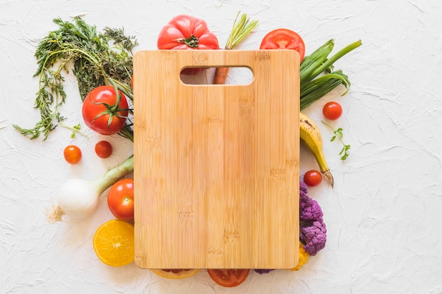 Tábua de cortar de madeira sobre os legumes no pano de fundo de textura