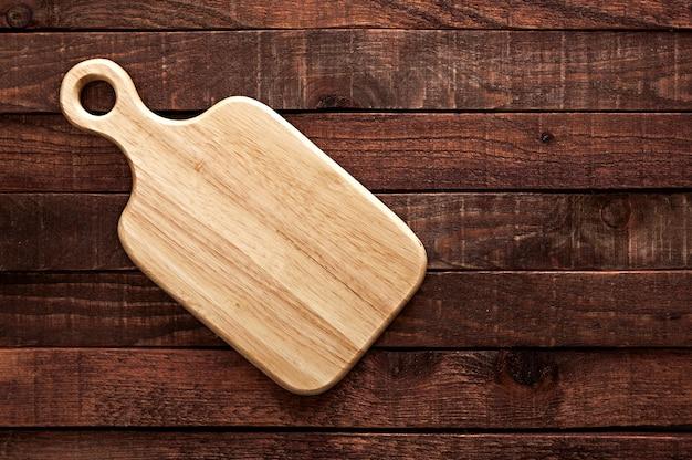 Tábua de cortar na mesa de madeira velha escura