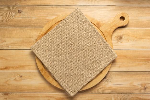 Tábua de cortar pizza e naplin no fundo da prancha de madeira rústica, vista superior