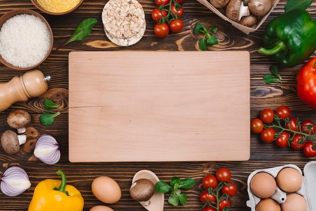 Tábua de cortar rodeada de legumes; ovos e grãos de arroz na mesa