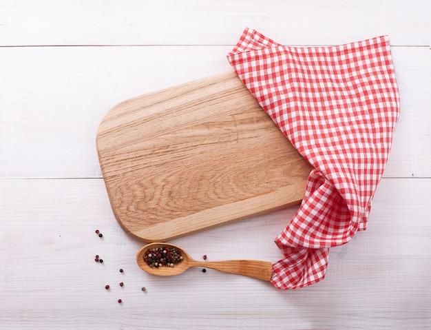 Tábua de cortar vazia com guardanapo na mesa de madeira