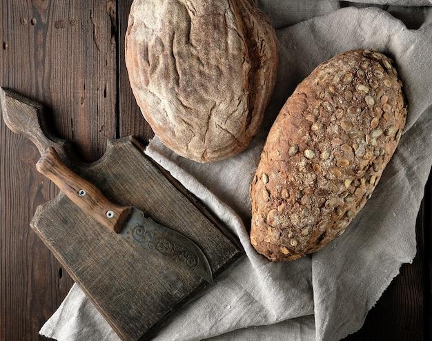 Tábua de cortar velha, faca e dois pães de pão integral
