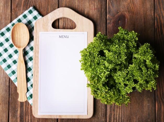 Tábua de corte com folha de papel de menu, com alface na superfície de pranchas de madeira
