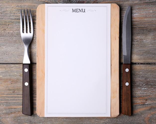 Tábua de corte com folha de papel do menu em pranchas de madeira rústicas