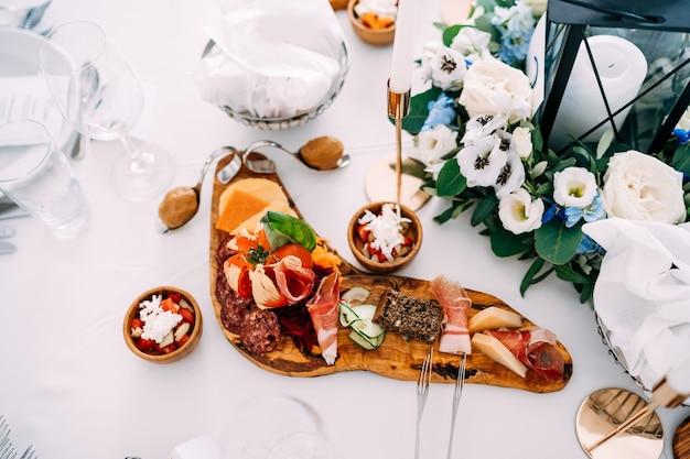 Tábua de corte com presunto fatiado, linguiça e queijo na mesa