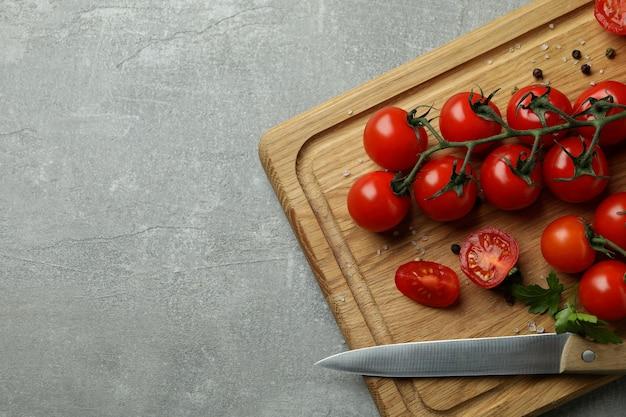 Tábua de corte com tomate cereja e faca em plano de fundo texturizado cinza