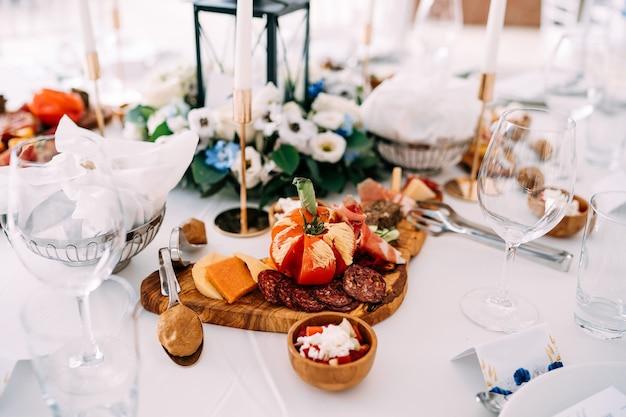 Tábua de corte com um tomate cortado em pedaços de linguiça e presunto em uma mesa com taças de copos