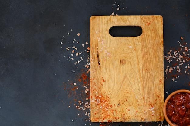 Tábua de corte de madeira e molho de salsa em uma travessa. utensílios de cozinha e culinária de alimentos