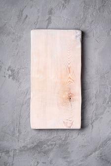 Tábua de corte de madeira velha branca artesanal na superfície de concreto de pedra