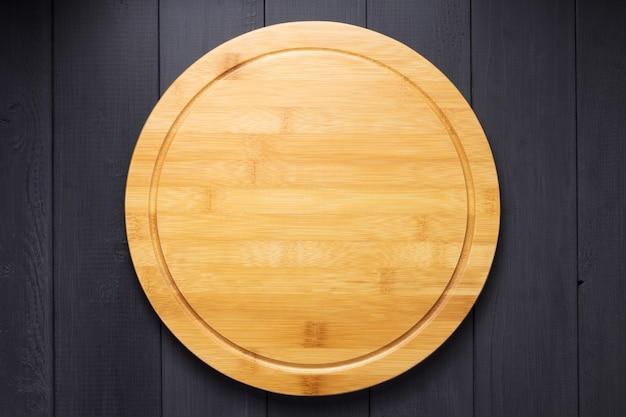 Tábua de corte de pizza no fundo de uma prancha de madeira rústica, vista superior