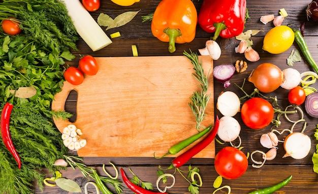 Tábua de corte em branco cercada por pimentas, ervas, tomates, cogumelos e outros vegetais saborosos