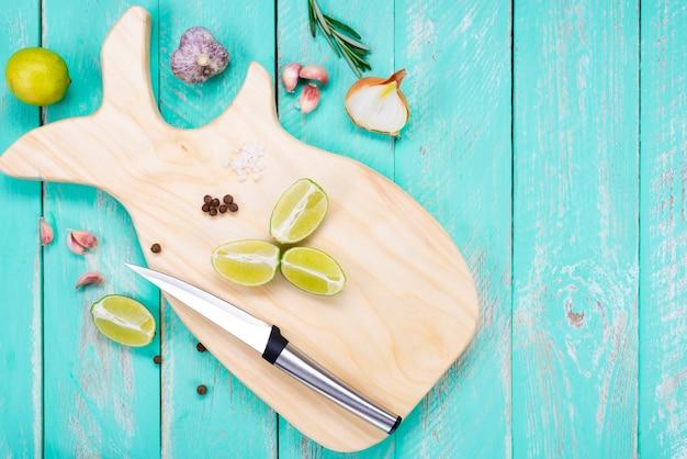 Tábua de corte em forma de baleia com uma faca em uma mesa de madeira vintage