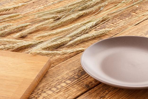 Tábua de corte, prato e espigas de cevada em um fundo de madeira.