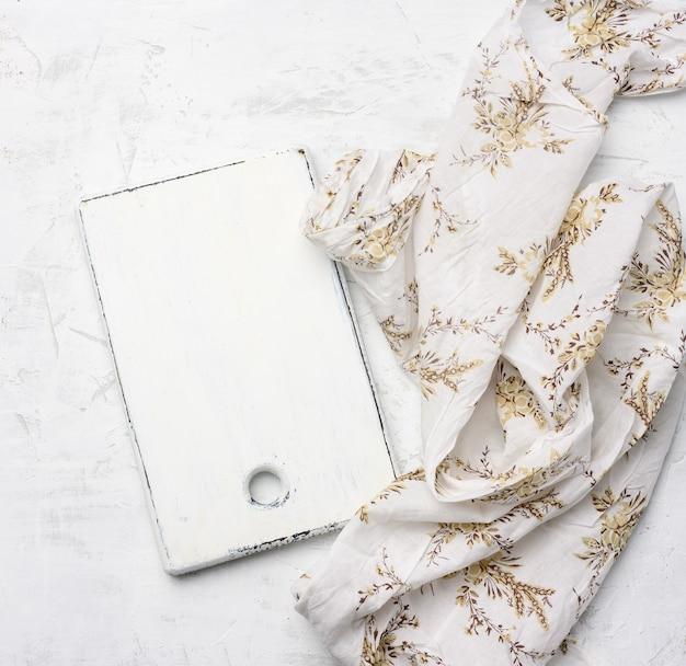 Tábua de corte retangular branca em toalha de mesa de tecido branco, vista de cima, espaço vazio